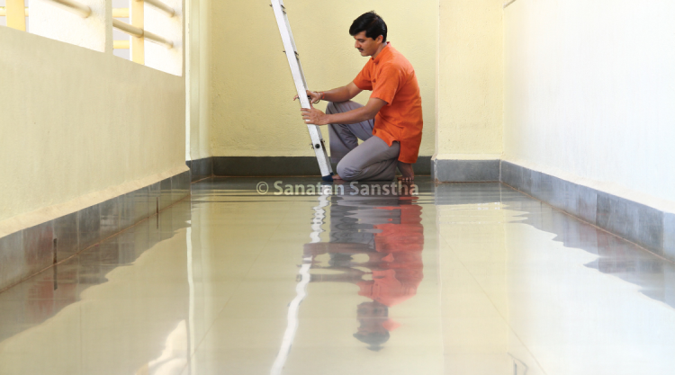 Watery surface on corridor tiles : A seeker fixing the ladder to the loft in one of the corridors. Observe the watery kind of surface and colours in the reflection